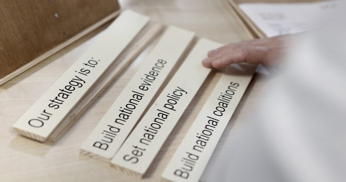 "Wooden blocks reading ""Our strategy is to: Build national evidence; set national policy; build national coalitions"""