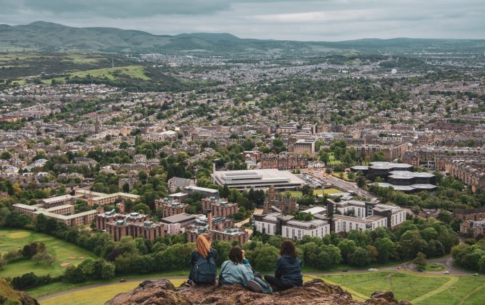 Three friends sit looking out over Edinburgh from Arthurs seat